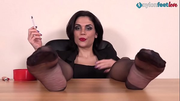 hot-brunette-smokes-a-cig-with-her-nylon-feet-up-on-a-desk